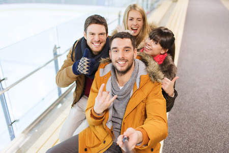 Photo for people, friendship, technology and leisure concept - happy friends taking selfie with camera or smartphone and selfie stick on skating rink - Royalty Free Image