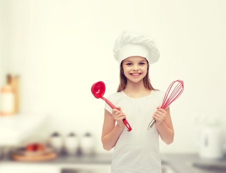 Foto de cooking and people concept - smiling little girl in cook hat with ladle and whisk - Imagen libre de derechos