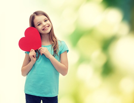 Foto de love, happiness and people concept - smiling little girl with red heart - Imagen libre de derechos