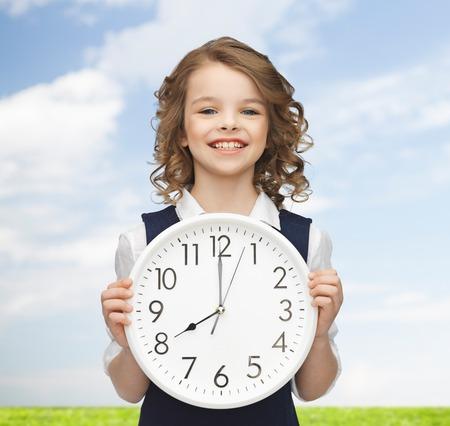 Photo pour people, time management and children concept - smiling girl holding big clock showing 8 o'clock - image libre de droit