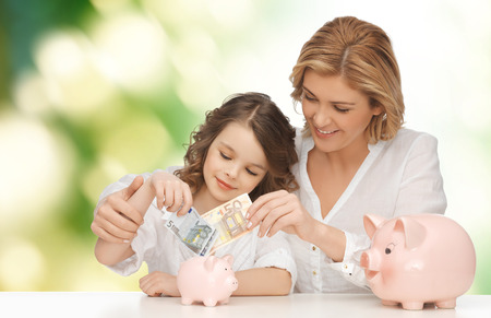 Foto de people, finances, family budget and savings concept - happy mother and daughter with piggy banks and paper money over green background - Imagen libre de derechos