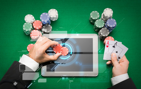 Foto de casino, online gambling, technology and people concept - close up of poker player with playing cards, tablet pc computer and chips at green casino table - Imagen libre de derechos