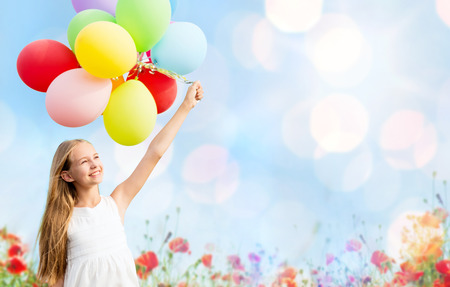 Photo for summer holidays, celebration, children and people concept - happy girl with colorful balloons over blue lights and poppy field background - Royalty Free Image