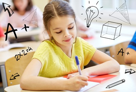 Photo pour education, elementary school, learning and people concept - group of school kids with notebooks writing test in classroom over doodles - image libre de droit