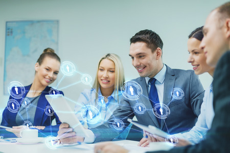 Foto de business, technology, connection, communication and people concept - smiling business team with tablet pc computer and virtual contacts projection having discussion in office - Imagen libre de derechos