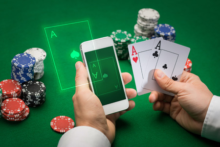 Foto de casino, online gambling, technology and people concept - close up of poker player with playing cards, smartphone and chips at green casino table - Imagen libre de derechos