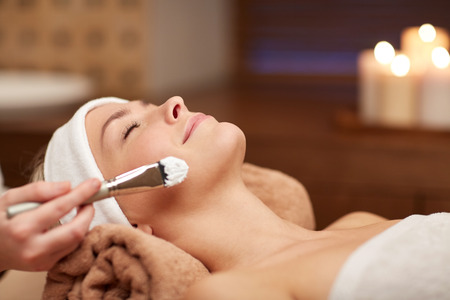 Photo pour people, beauty, spa, cosmetology and skincare concept - close up of beautiful young woman lying with closed eyes and cosmetologist applying facial mask by brush in spa - image libre de droit