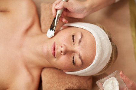 Foto de people, beauty, spa, cosmetology and skincare concept - close up of beautiful young woman lying with closed eyes and cosmetologist applying facial mask by brush in spa - Imagen libre de derechos