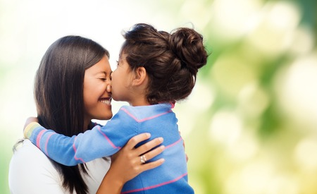 Photo pour family, children and happy people concept - happy little girl hugging and kissing her mother over green background - image libre de droit