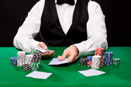 Foto de casino, gambling, poker, people and entertainment concept - close up of holdem dealer with playing cards and chips on green table - Imagen libre de derechos