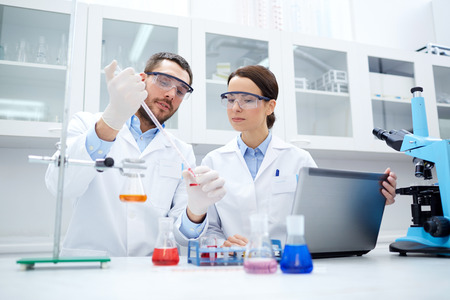 Foto de science, chemistry, technology, biology and people concept - young scientists with pipette and glass making test or research in clinical laboratory - Imagen libre de derechos