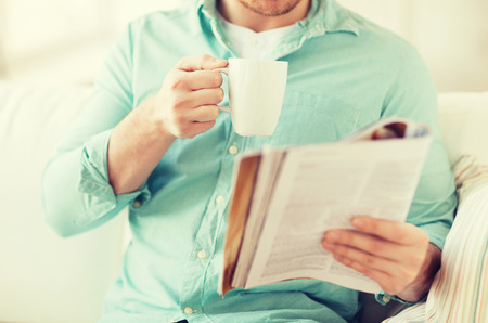 Foto de home, rest, news, drinks and people concept - close up of man reading magazine and drinking from cup sitting on couch at home - Imagen libre de derechos