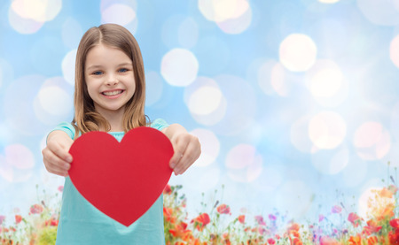 Foto de love, charity, holidays, children and people concept - smiling little girl with red heart over blue lights and poppy field background - Imagen libre de derechos
