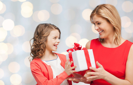 people, holidays, christmas and family concept - happy mother and daughter giving and receiving gift box over holiday lights background