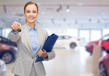 Foto de auto business, car sale, gesture and people concept - happy businesswoman or saleswoman with folder giving car key over auto show background - Imagen libre de derechos