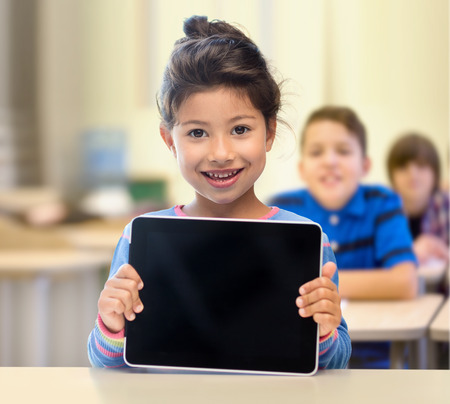 Foto de education, elementary school, technology, advertisement and children concept - little student girl showing blank black tablet pc computer screen over classroom and classmates background - Imagen libre de derechos