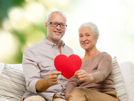 Foto de family, holidays, age and people concept - happy senior couple holding little red paper heart shape cutout and sitting on sofa over green background - Imagen libre de derechos