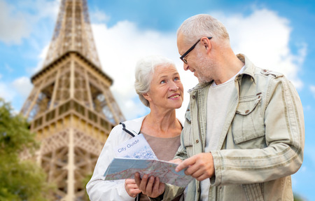 Foto de family, age, tourism, travel and people concept - senior couple with map and city guide over eiffel tower and blue sky background - Imagen libre de derechos