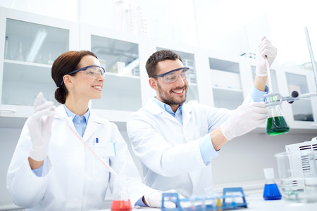 Foto de science, chemistry, technology, biology and people concept - young scientists with pipette and flask making test or research in clinical laboratory - Imagen libre de derechos