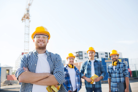 Photo pour business, building, teamwork and people concept - group of smiling builders in hardhats with clipboard outdoors - image libre de droit