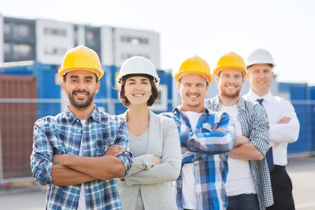 Foto de business, building, teamwork and people concept - group of smiling builders in hardhats outdoors - Imagen libre de derechos