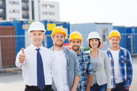 Foto de business, building, teamwork, gesture and people concept - group of smiling builders in hardhats showing thumbs up outdoors - Imagen libre de derechos