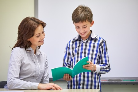 Foto de education, elementary school, learning, examination and people concept - school boy with notebook and teacher in classroom - Imagen libre de derechos
