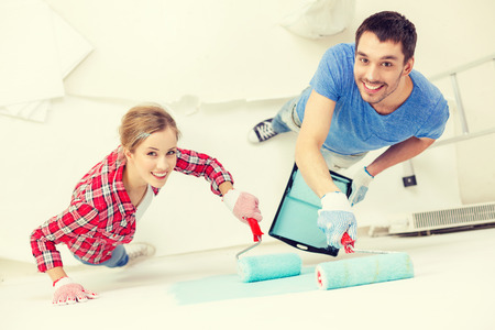 Photo for repair, building and home concept - smiling couple painting wall at home - Royalty Free Image