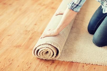 Photo pour repair, building and home concept - close up of male hands unrolling carpet - image libre de droit