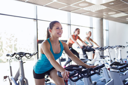 Foto de sport, fitness, lifestyle, equipment and people concept - group of women riding on exercise bike in gym - Imagen libre de derechos