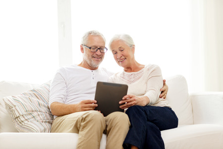 Photo pour family, technology, age and people concept - happy senior couple with tablet pc computer at home - image libre de droit