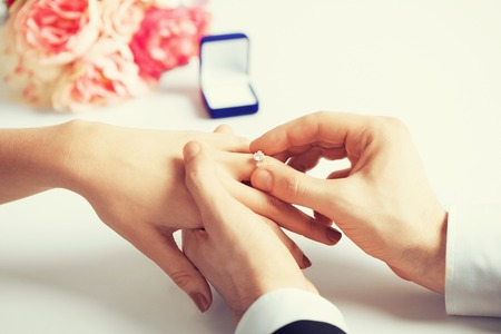 Photo pour picture of man putting  wedding ring on woman hand - image libre de droit