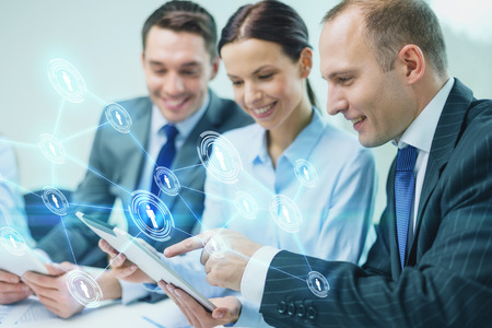 Foto per business, technology, connection, communication and people concept - smiling business team with tablet pc computer and virtual contacts projection having discussion in office - Immagine Royalty Free