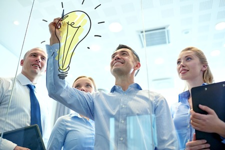 Foto de business, people, teamwork and planning concept - smiling business team with marker and light bulb doodle working in office - Imagen libre de derechos