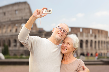 Foto de age, tourism, travel, technology and people concept - senior couple with camera taking selfie on street over coliseum background - Imagen libre de derechos