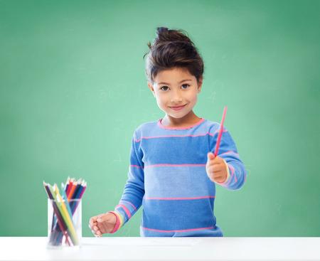 Foto de education, school, children, creativity and happy people concept - happy little girl drawing with coloring pencils over green chalk board background - Imagen libre de derechos