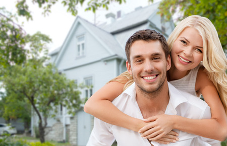 Foto de love, people, real estate, home and family concept - smiling couple hugging over house background - Imagen libre de derechos