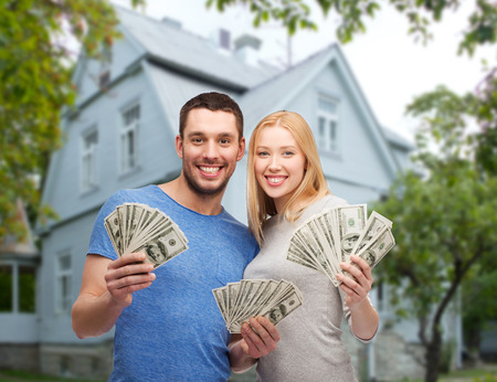 Photo pour love, people, real estate, home and family concept - smiling couple showing dollar cash money over house background - image libre de droit