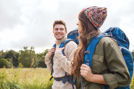 Foto de adventure, travel, tourism, hike and people concept - smiling couple walking with backpacks outdoors - Imagen libre de derechos