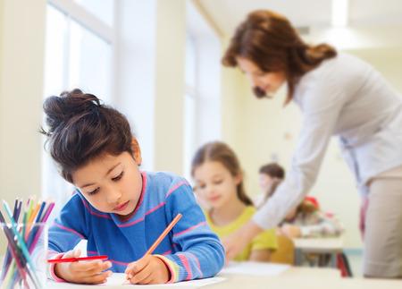 Foto de education, elementary school, children, creativity and people concept - happy little girl drawing with coloring pencils over classroom and teacher background - Imagen libre de derechos