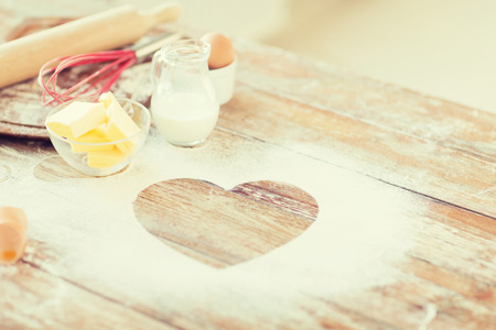 Foto de cooking and love concept - close up of heart of flour on wooden table at home - Imagen libre de derechos