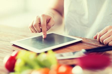 Foto de cooking, technology and home concept - closeup of man pointing finger to tablet pc computer - Imagen libre de derechos