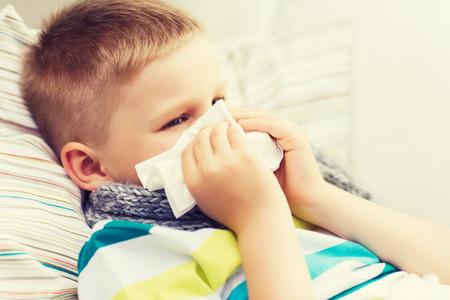 Foto de childhood, healthcare and medicine concept - ill boy with flu blowing nose at home - Imagen libre de derechos
