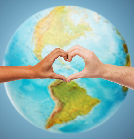 Photo pour people, peace, love, life and environmental concept - close up of human hands showing heart shape gesture over earth globe and blue background - image libre de droit