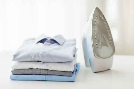 Foto de ironing, clothes, housework and objects concept - close up of iron and clothes on table at home - Imagen libre de derechos