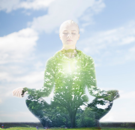 Foto de sport, fitness, yoga, double exposure and people concept - happy young woman meditating in lotus pose over blue sky and green tree background - Imagen libre de derechos