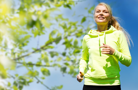 Photo for fitness, people and healthy lifestyle concept - happy young female runner jogging outdoors - Royalty Free Image
