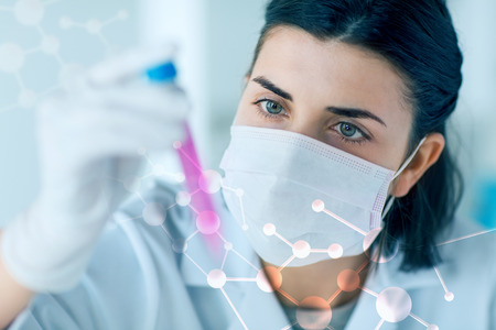 Foto de science, chemistry, biology, medicine and people concept - close up of young female scientist holding tube with sample making and test or research in clinical laboratory - Imagen libre de derechos