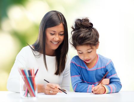 Foto de family, children, creativity and happy people concept - happy mother and daughter drawing with pencils over green background - Imagen libre de derechos