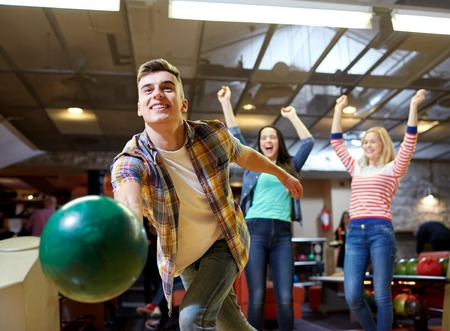 Photo pour people, leisure, sport and entertainment concept - happy young man throwing ball in bowling club - image libre de droit